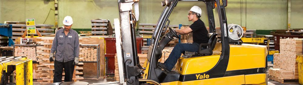two workers in the Los Angeles steel service center, one is driving a skid loader of equipment