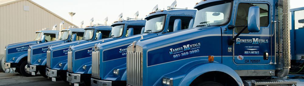 6 shiny blue James Metals trucks parked in front of the steel warehouse